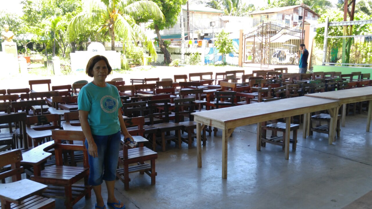 """Teacher Celia Alvarez showed us all the chairs moved out of the classrooms, the kids are being taught under the overhang"""
